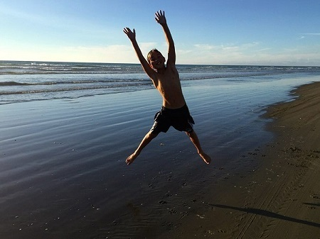 Child jumping on beach