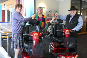 Photo of Raewyn Cameron, Wendy Cutler and Lew Findlay with the mobility scooters